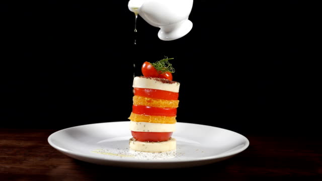 Pouring olive oil on mozzarella salad in slow motion. food footage on black background. Italian caprese salad with cheese. Healthy food and vegetarian concept. Full hd