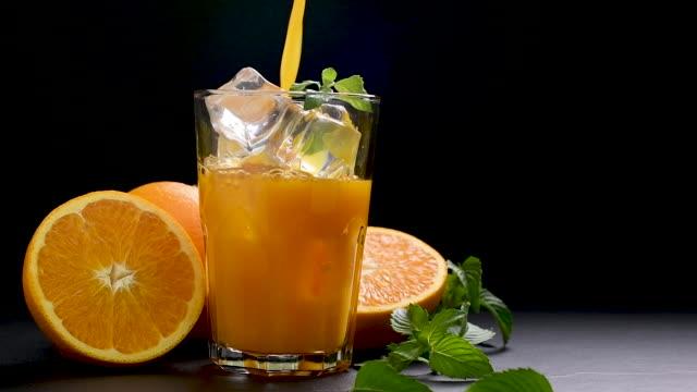 Pouring Orange juice into glass - slow motion