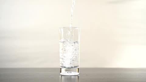vidéos et rushes de verser débordant verre d'eau au ralenti. - en verre