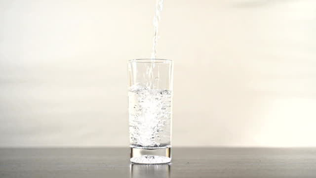 pouring overflowing glass of water in slow motion. - glas porslin bildbanksvideor och videomaterial från bakom kulisserna