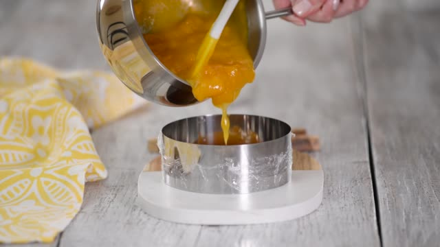 pouring peach jelly into the metal ring. making peach filling for mousse cake - sostanza gelatinosa video stock e b–roll