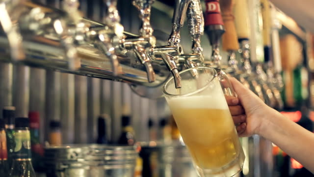 vídeos de stock e filmes b-roll de pouring perfect draft beer. a beer tap is a valve, specifically a tap, for controlling the release of beer - cerveja