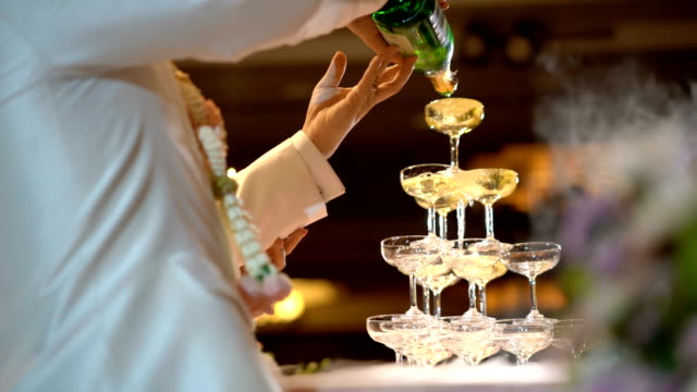 vídeos de stock e filmes b-roll de 4k pouring pyramid champagne glasses in wedding ceremony - champanhe