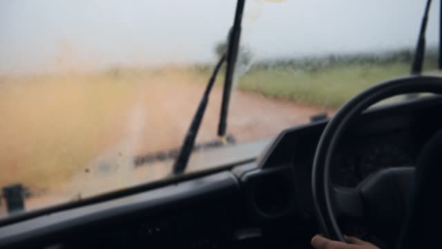 Pouring rain in rainy season in the savanna in Kenya, from driving inside a safari truck vehicle, Africa Pouring rain in rainy season in the savanna in Kenya, from driving inside a safari truck vehicle, Africa mud stock videos & royalty-free footage