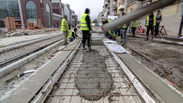 コンクリート ミキサー タイムラプス hyperlapse によって道路に鉄筋を配置した後、生コンクリートを注ぐ - 支えられた点の映像素材/bロール