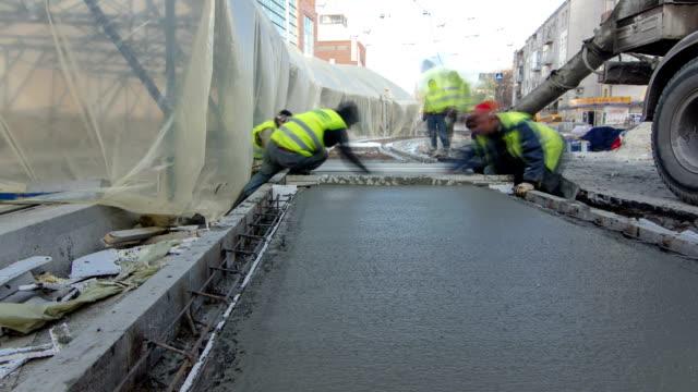 コンクリート ミキサー タイムラプス hyperlapse によって道路に鉄筋を配置した後、生コンクリートを注ぐ - セメント点の映像素材/bロール