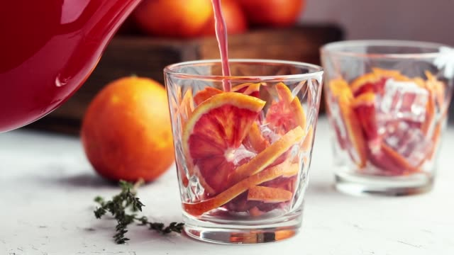 pouring red orange juice in a large glass or blood orange sparkling vodka cocktail or aperitif with campari - sicily filmów i materiałów b-roll
