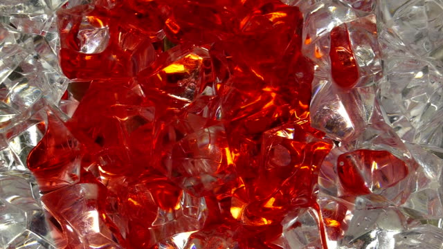 Pouring red water on ice cubes. video