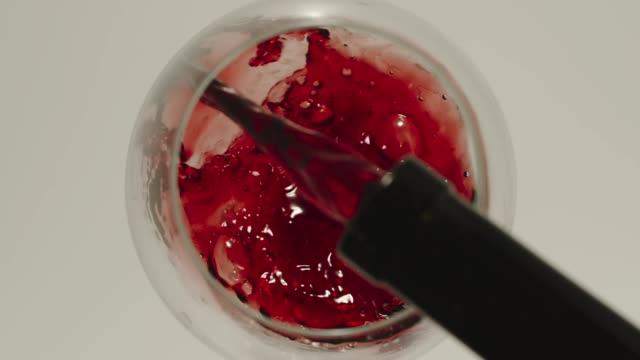 SLOW MOTION: Pouring red wine from a bottle into a glass - Top View SLOW MOTION: Pouring red wine from a bottle into a glass - Top View red wine stock videos & royalty-free footage