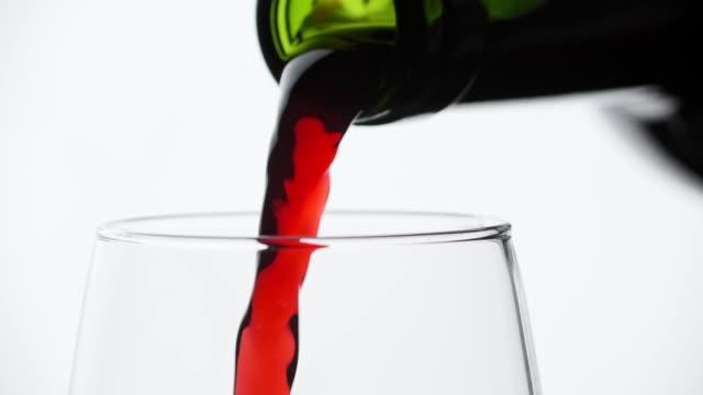 rotwein aus der flasche in den kelten gießen. nahaufnahme des weingießens im glas - cabernet sauvignon traube stock-videos und b-roll-filmmaterial