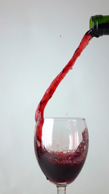 pouring red wine into a glass, gray background, super slow motion close up shot - vertical format video stock videos and b-roll footage