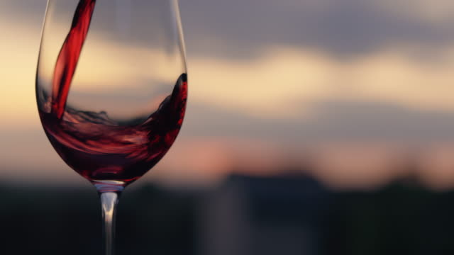 pouring red wine into a glass on at dusk - barile video stock e b–roll