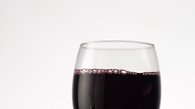 rotwein in ein glas gießen. top-ansicht von weinglas voller alkohol getränk auf weißem hintergrund - cabernet sauvignon traube stock-videos und b-roll-filmmaterial