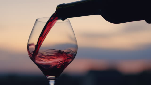 Pouring red wine into a glass Pouring red wine into a glass at sunset red wine stock videos & royalty-free footage