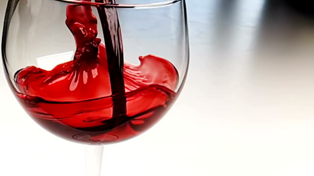 pouring red wine into drink glass on white background, nutrition health-care concept, shooting in slow motion pouring red wine into drink glass on white background, nutrition health-care concept, shooting with high speed camera in slow motion winetasting stock videos & royalty-free footage