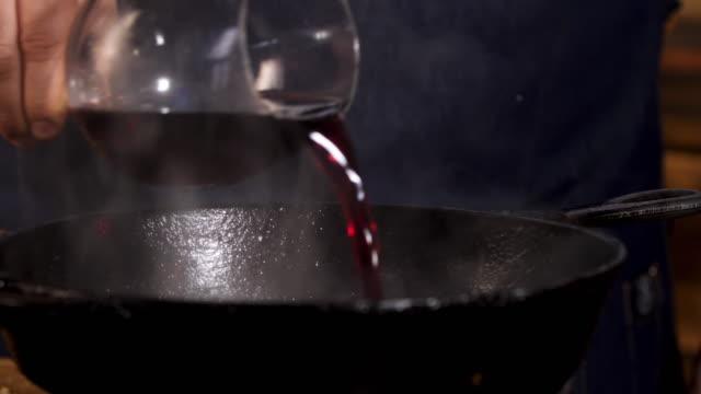 rotwein in die pfanne gießen. stock-footage. nahaufnahme des kochs männliche hände hinzufügen von rotwein in schwarze eisenpfanne für das kochen spezielle sauce - plus stock-videos und b-roll-filmmaterial