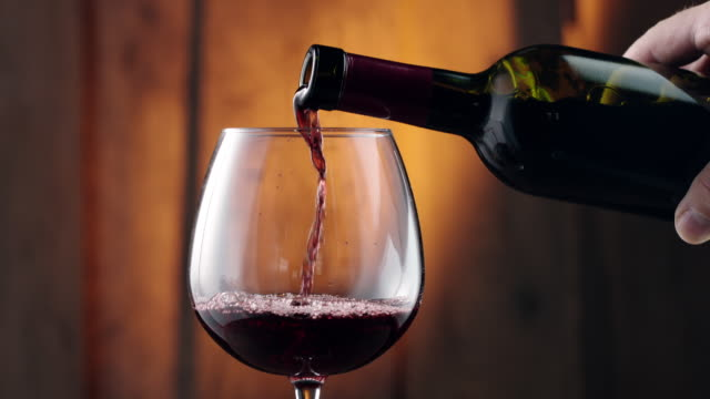 Pouring red wine into glass Close-up, pouring red wine from wine bottle into glass bottle stock videos & royalty-free footage