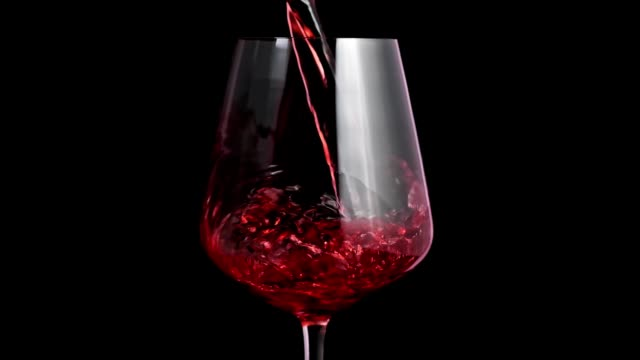 Pouring red wine into goblet. Close-up of red wine forms beautiful wave in glass