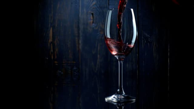 Pouring red wine into the glass against dark wooden background. Slow motion video