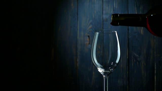 주둥이 레드 와인 을 유리컵 에 대 한 어둡습니다 목재 배경. 슬로우모션 - 와인병 스톡 비디오 및 b-롤 화면