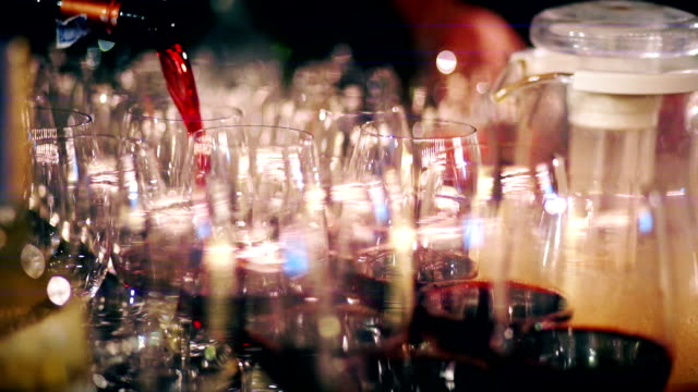 Pouring red wine into the wine glasses. video