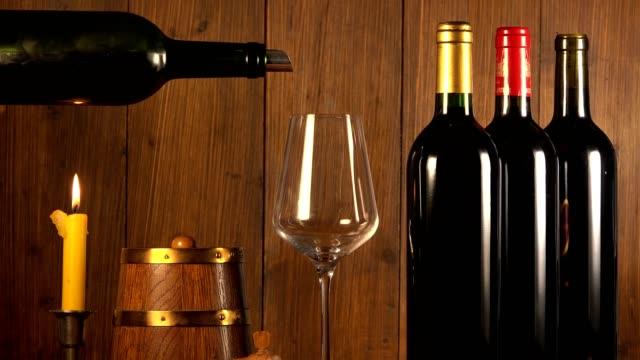 Verser le vin rouge dans le verre de vin de la bouteille verte, fond brun - Vidéo