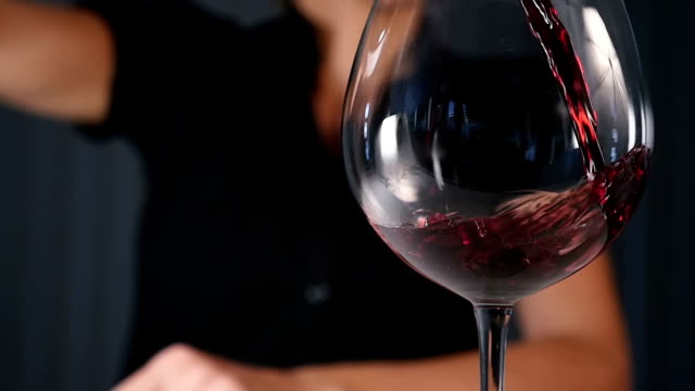 Pouring red wine Hd slow motion video close-up of unrecognizable person-woman pouring a wineglass of red wine in slow motion. Space for copy. red wine stock videos & royalty-free footage