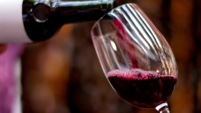 Pouring red winein a glass Close up of a person pouring red wine in a glass red wine stock videos & royalty-free footage