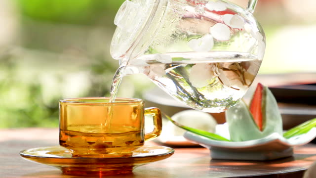 4K Pouring Sakura Flowering Tea in Japanese garden background