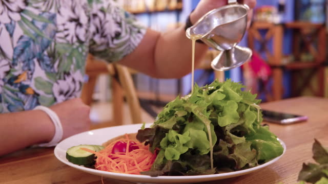 野菜サラダにサラダクリームソースを注ぎます。 - ベジタリアン料理点の映像素材/bロール