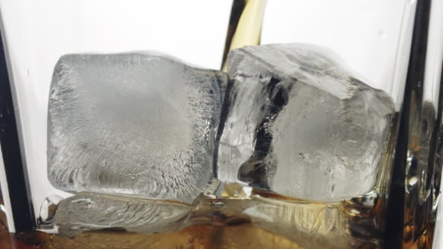 Pouring Scotch whiskey into glass with ice cubes video