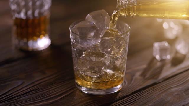 versare whisky scotch in vetro con cubetti di ghiaccio - rum superalcolico video stock e b–roll