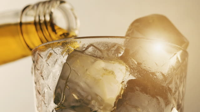 pouring scotch whisky in glass with ice cubes - whisky video stock e b–roll