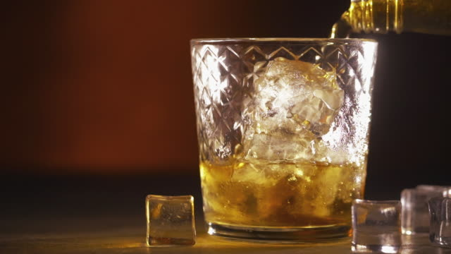 pouring scotch whisky in glass with ice cubes - rum superalcolico video stock e b–roll