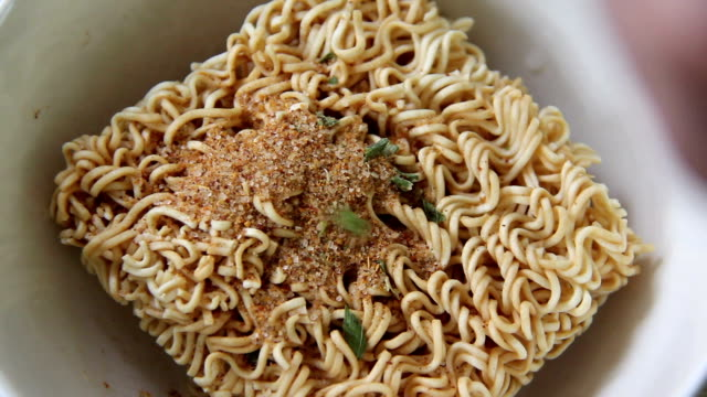 pouring seasoning over noodle video