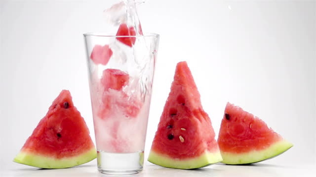 Pouring Soda Water with the Ice and Watermelon Cubes into a Glass video