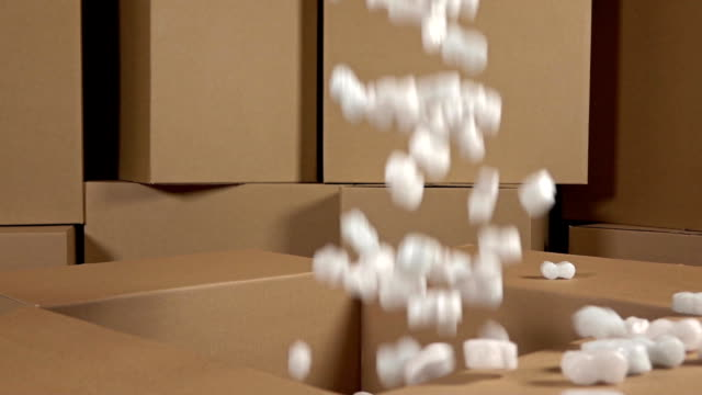 vídeos de stock e filmes b-roll de pouring soft polystyrene pieces into big carton. shockproof packaging material. safety, security and insurance concepts. slow motion video - packaging