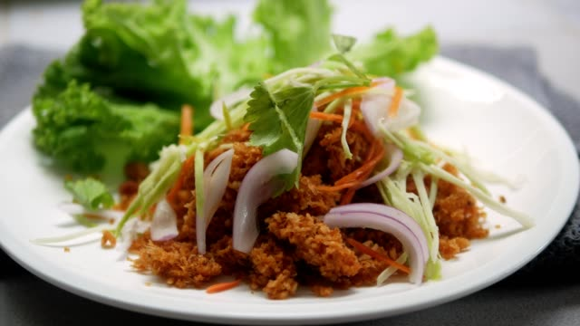 pouring spicy sour sauce to fried catfish spicy salad,  thai food. - siluriformes video stock e b–roll