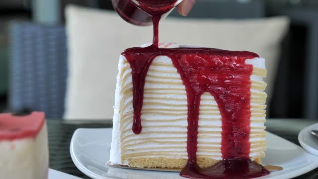 pouring strawberry jam on cheese cake - sernik filmów i materiałów b-roll