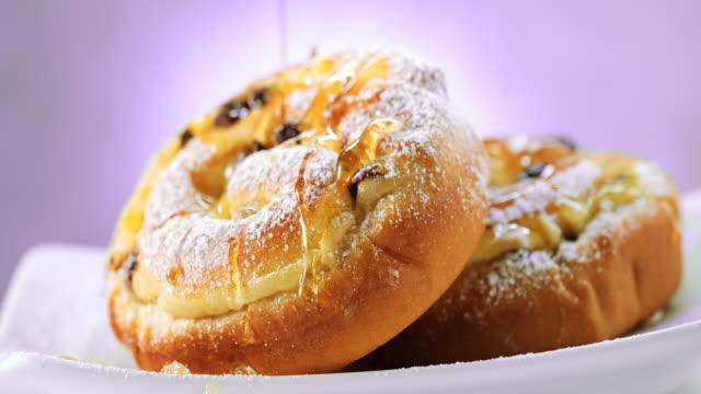 pouring syrup on to raisin - chocolate brioche buns - sliding shot - sciroppo video stock e b–roll