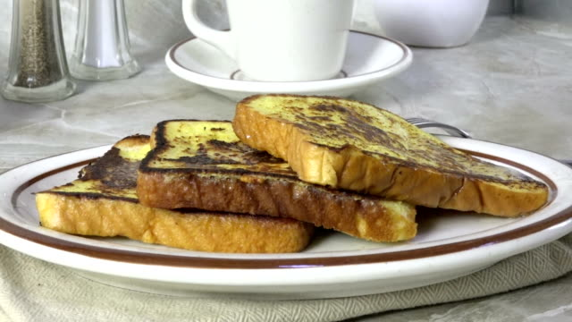 Pouring syrup onto French toast