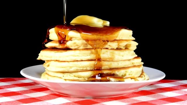 versare lo sciroppo sopra pancake - pancake video stock e b–roll