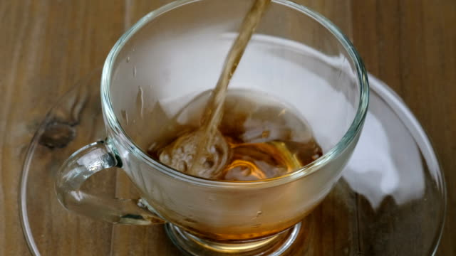 Pouring tea - Hot tea flowing from teapot to teacup video