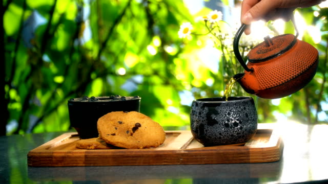 Pouring Tea Into Teapot With Cookies Outdoors