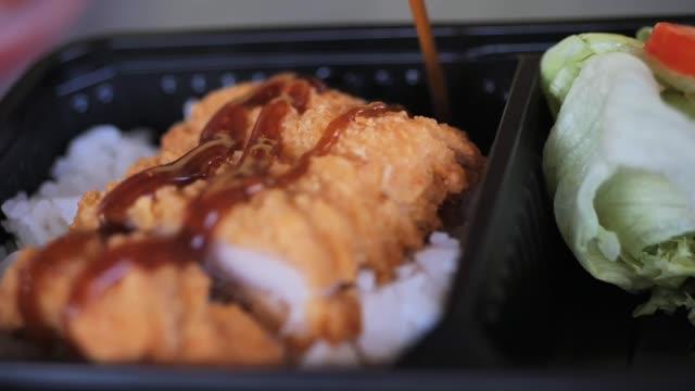 vídeos de stock e filmes b-roll de pouring teriyaki sauce on fried pork rice lunchbox, slow motion. - comida asiática