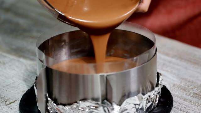 vídeos y material grabado en eventos de stock de verter el mousse de chocolate en la forma. - suflé