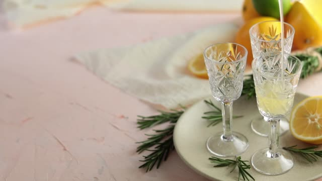 Pouring traditional italian homemade lemon alcohol drink liqueur limoncello with pieces of lemon and rosemary herb on light pink, peach or coral color stone concrete surface. video