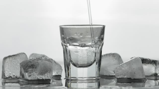 pouring up shot of vodka from a bottle into glass. white background - vodka video stock e b–roll