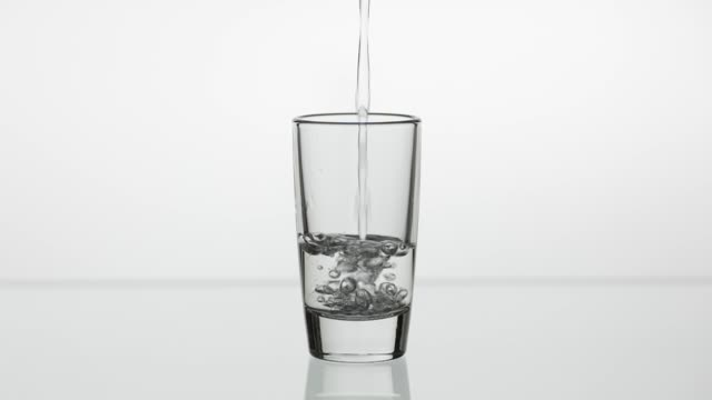 Pouring up shot of vodka into drinking glass. Slow motion. White background