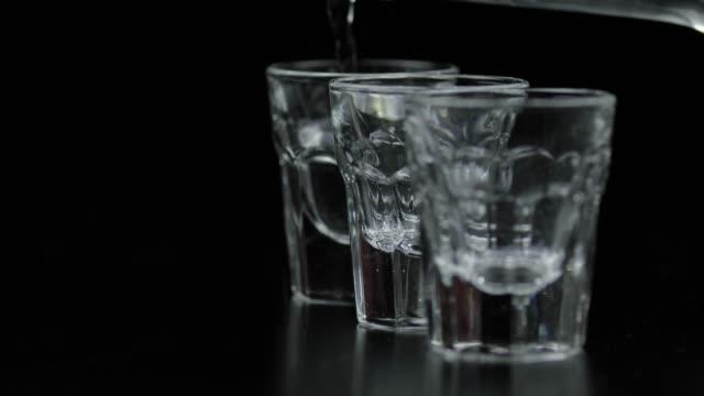 versando tre bicchieri di vodka da una bottiglia in vetro. sfondo nero - vodka video stock e b–roll